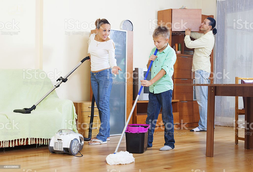 family of three with teenager doing housework stock photo