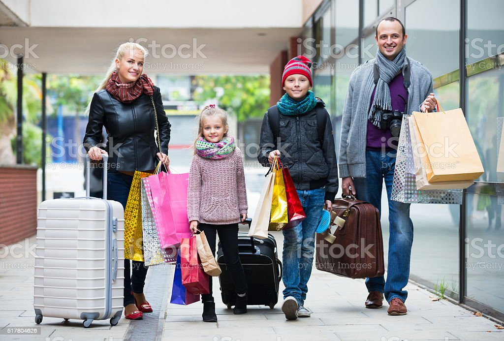 Family of tourists carrying shopping bags stock photo