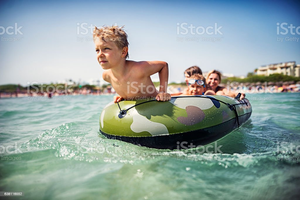 Family on a boat playing and having fun at sea stock photo