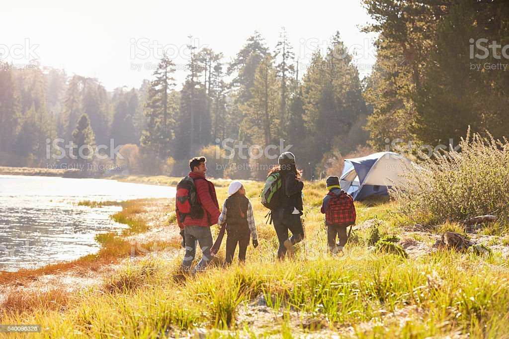 Family on a camping trip walking near a lake, back view stock photo