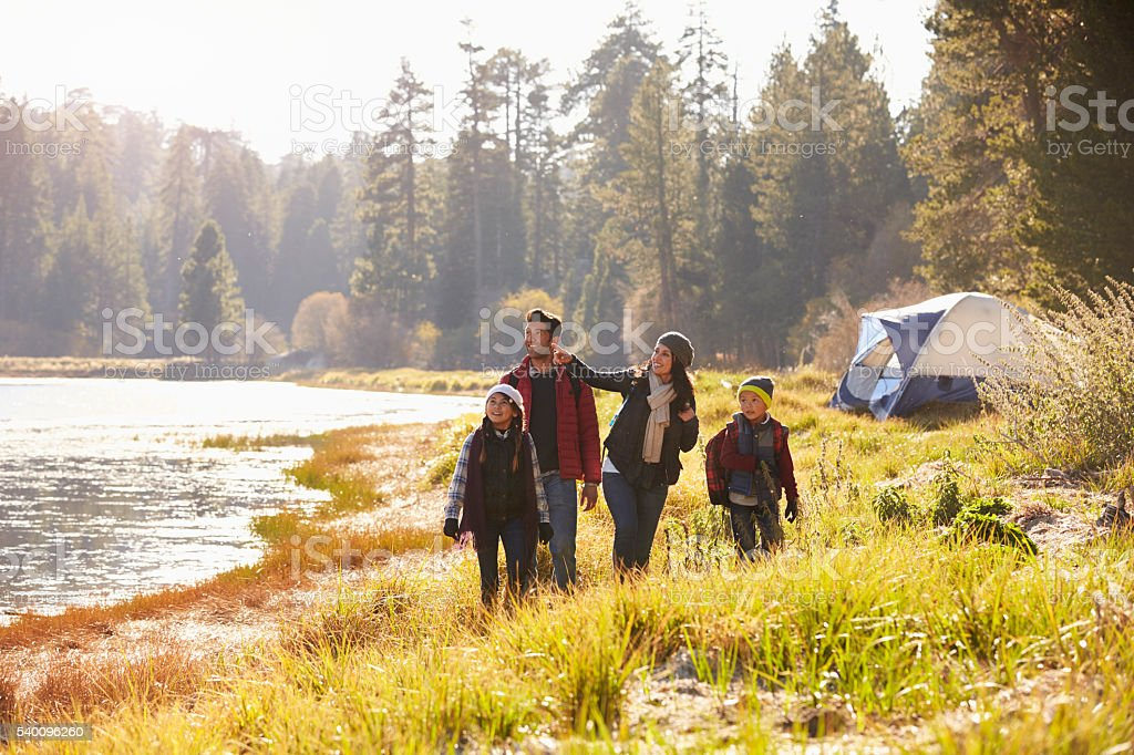 Family on a camping trip walking near a lake looking away stock photo