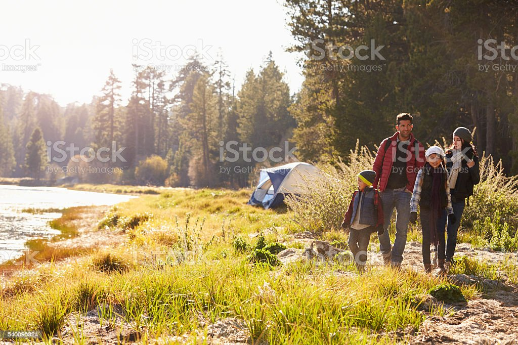 Family on a camping trip walking near a lake stock photo
