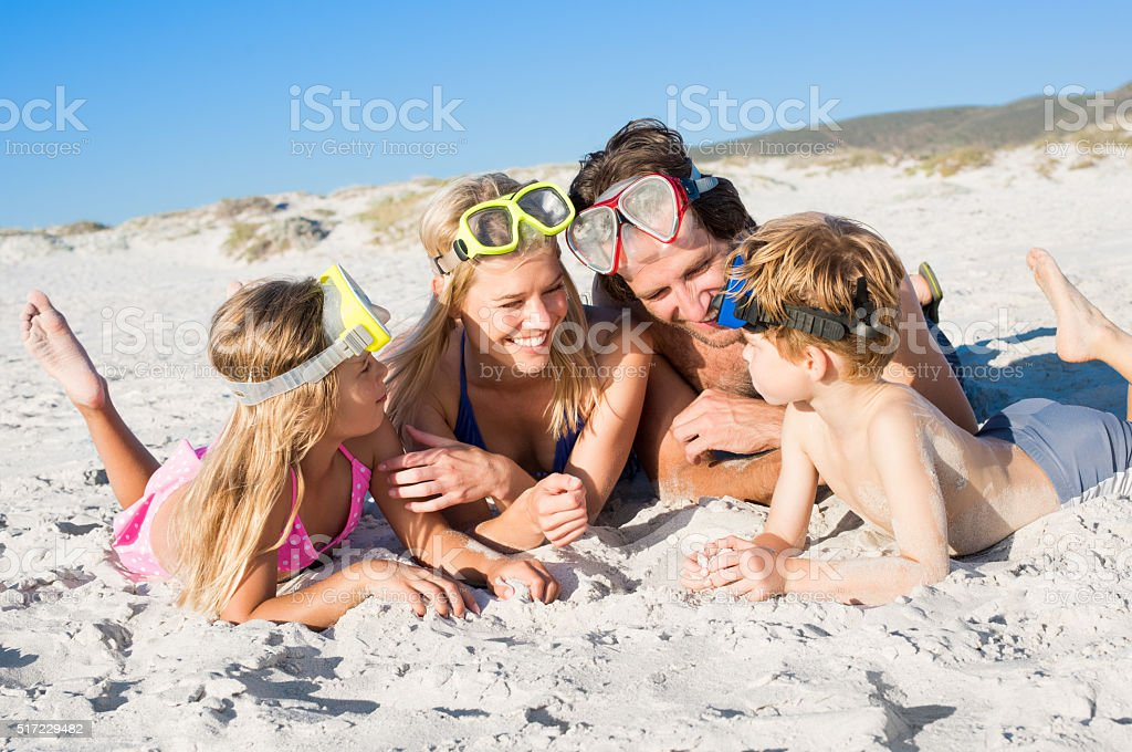 Family on beach with snorkeling masks stock photo