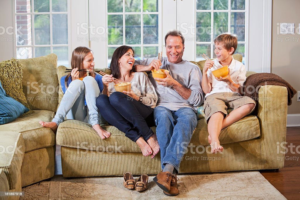 Family on couch, eating, talking royalty-free stock photo