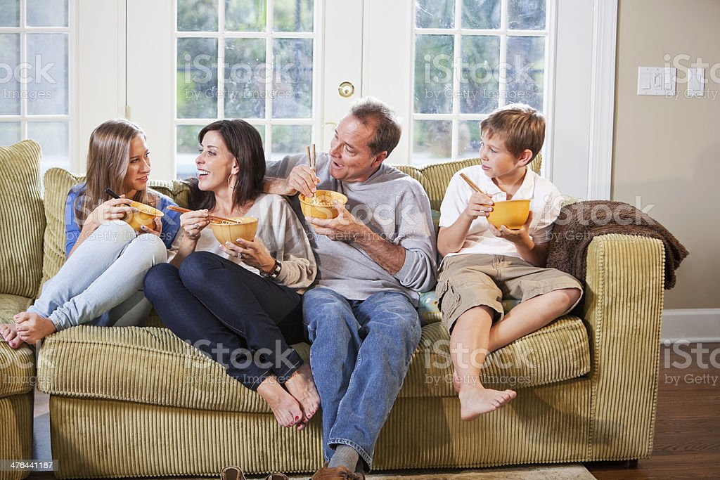Family on couch, eating, talking stock photo
