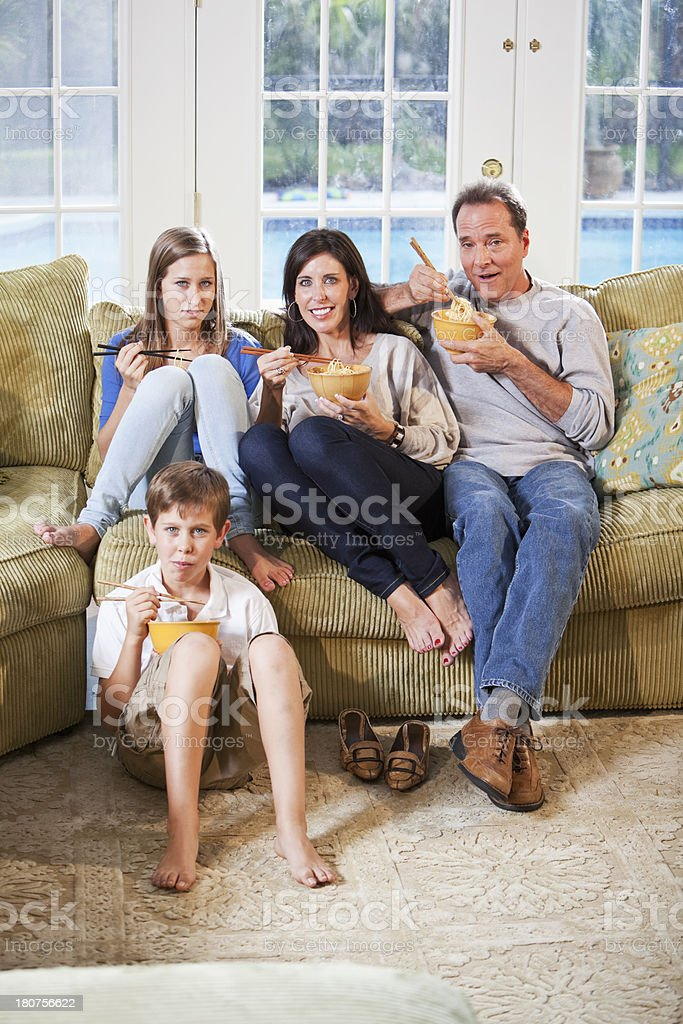 Family on couch, eating, watching tv stock photo