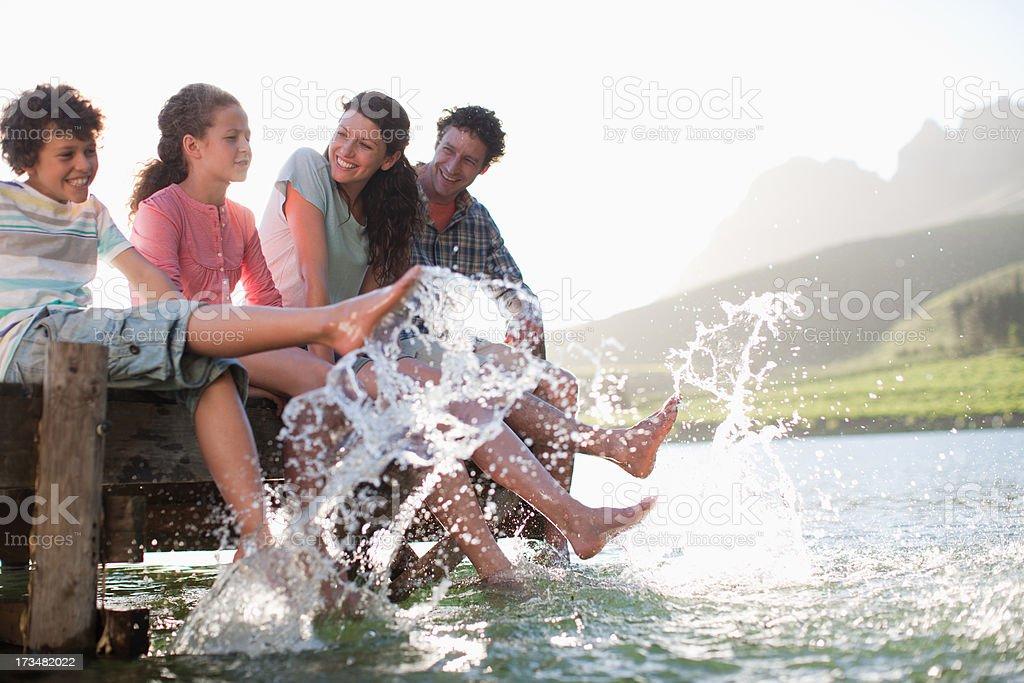 Family on dock splashing feet in lake stock photo