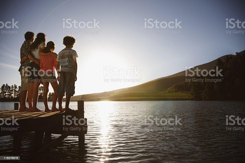 Family on dock watching sun set on lake stock photo
