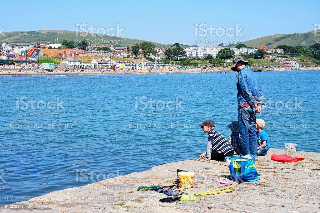 Family on harbour wall, Swanage. stock photo