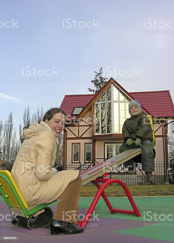 family on seesaw and home royalty-free stock photo
