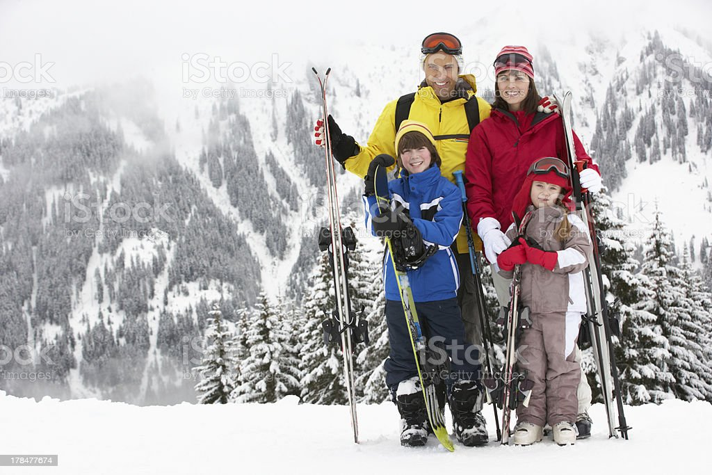 Family on ski holiday in the snow stock photo