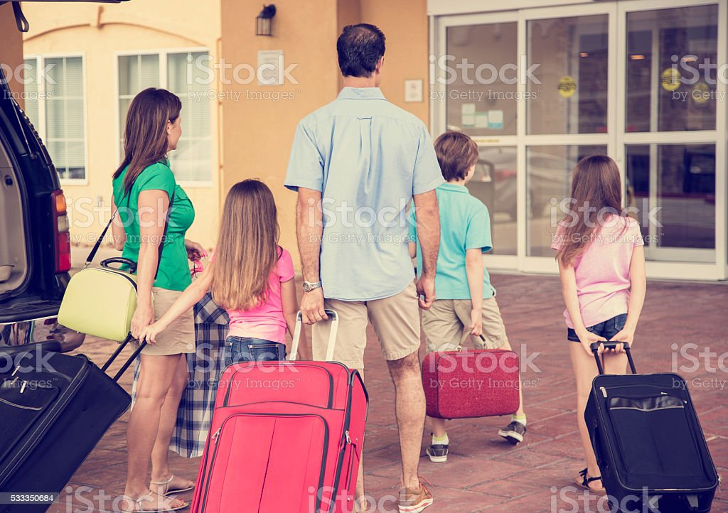 Family on summer vacation arrives at hotel. Luggage, resort entrance. stock photo