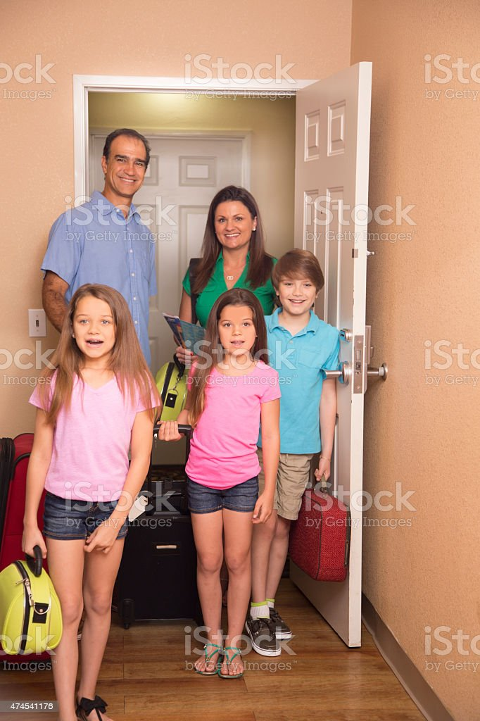 Family on summer vacation enters hotel room. Excited. stock photo