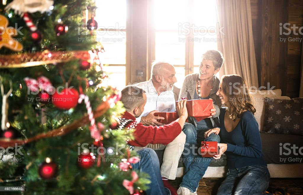 family on the living room exchancing christmas presents stock photo