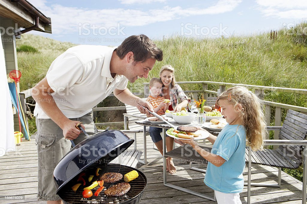 Family on vacation having barbecue royalty-free stock photo