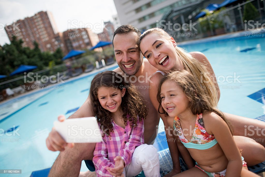 Family on vacation taking a selfie by the swimming pool stock photo