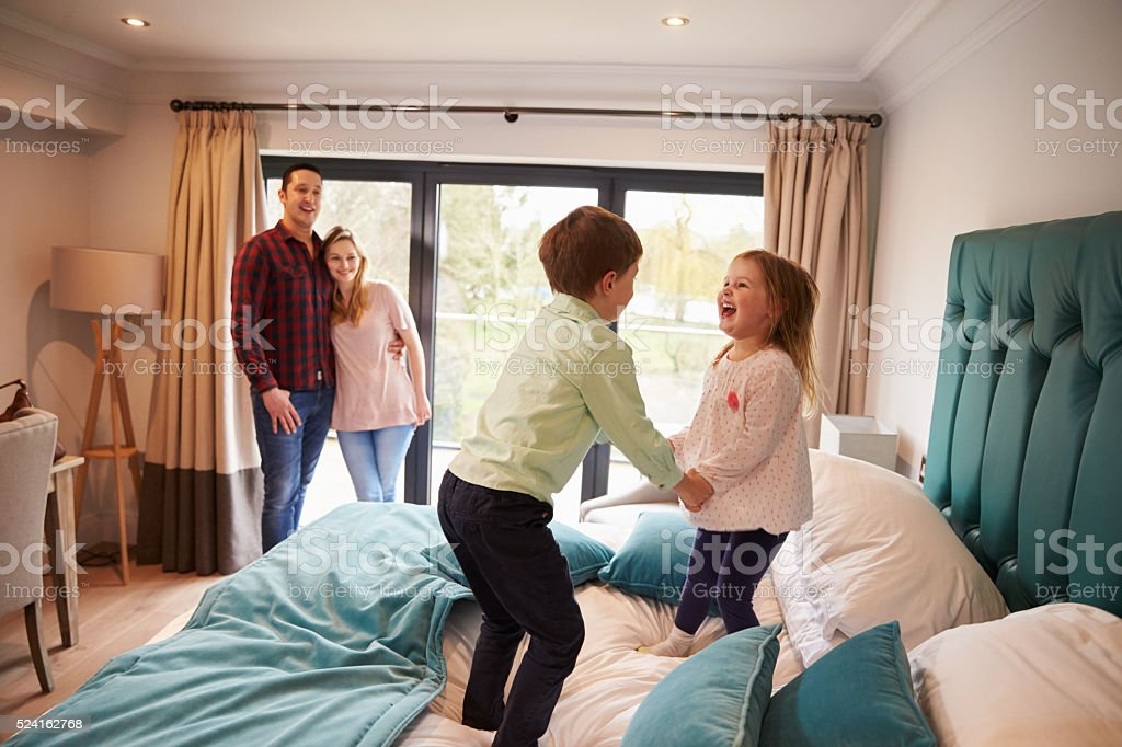 Family On Vacation With Children Playing On Hotel Bed stock photo