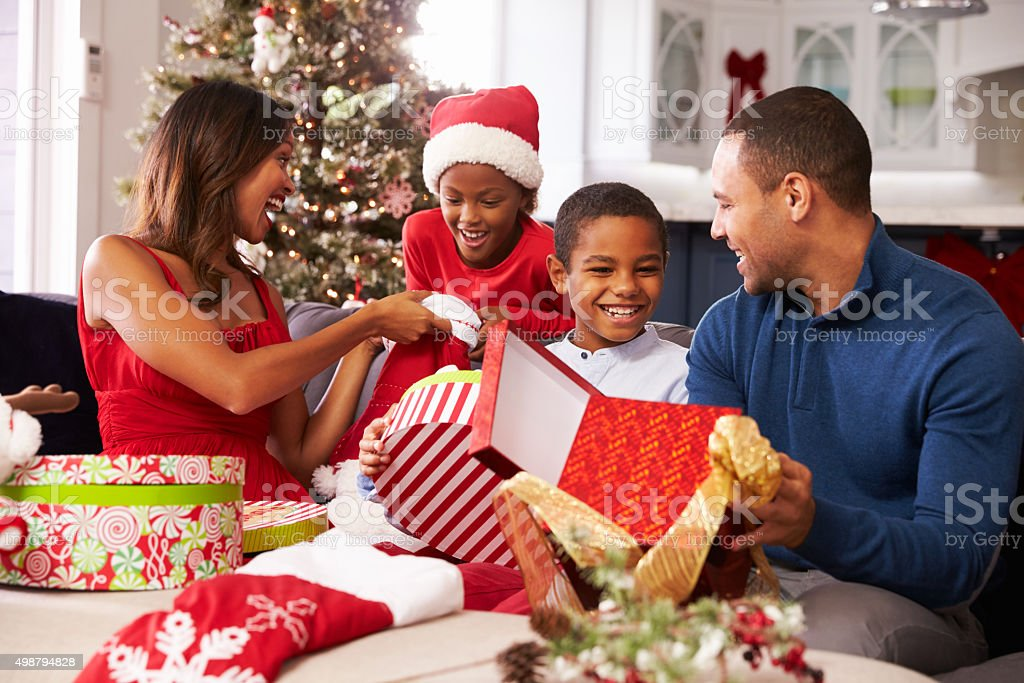 Family Opening Christmas Presents At Home Together stock photo