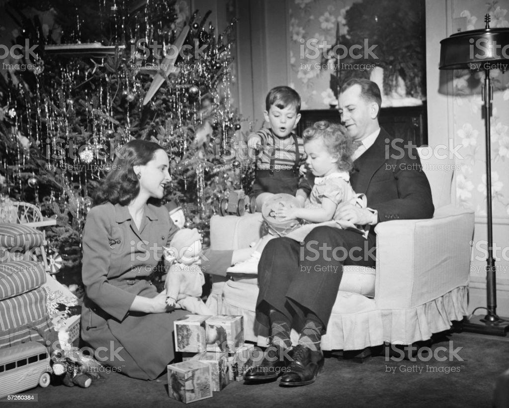 Family opening Christmas presents, children (2-3) (4-5), (B&W) stock photo
