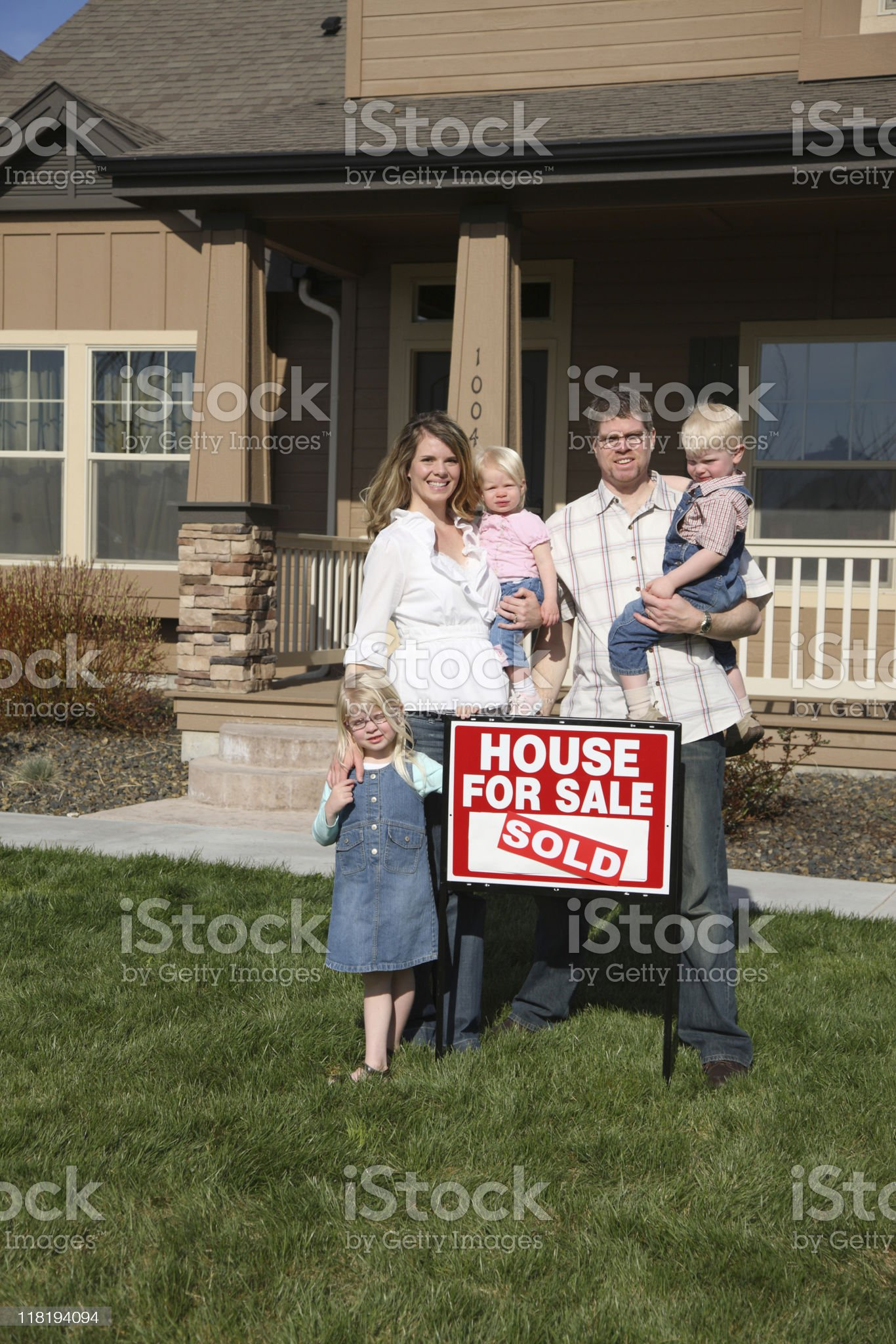 Family out in front of new home with SOLD sign royalty-free stock photo