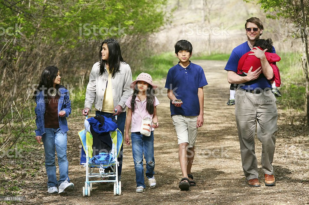 Family out walking together on quiet country path stock photo