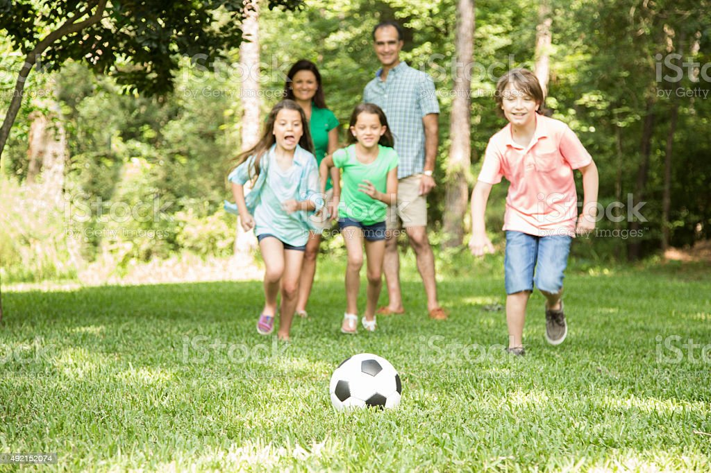 Family outdoors in spring, summer playing soccer game.  Park, yard. stock photo