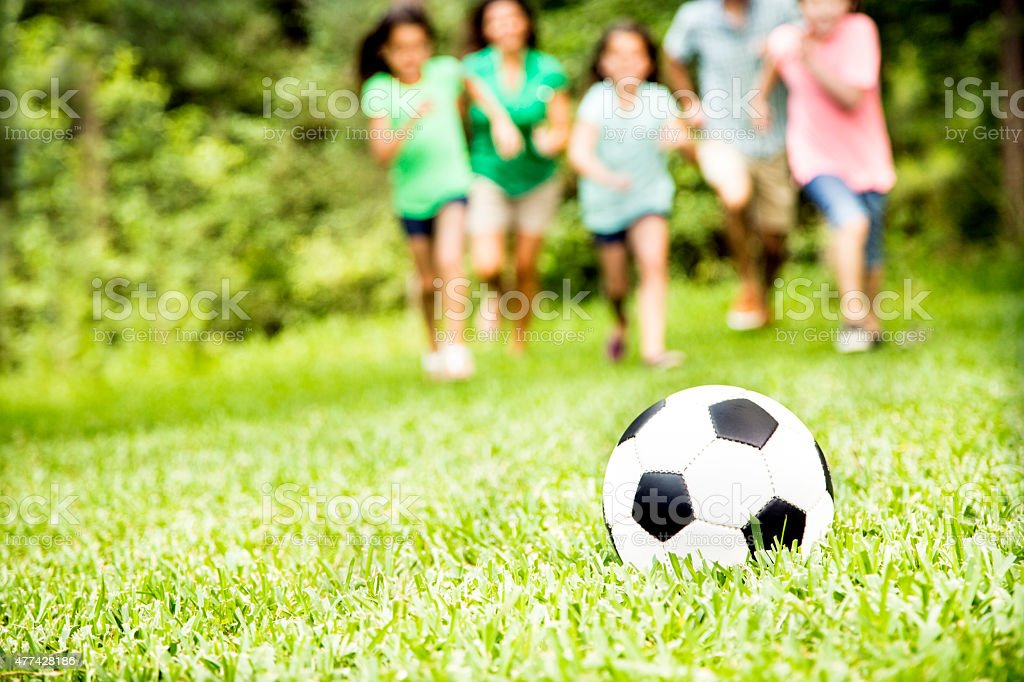 Family outdoors in summer playing soccer game. Park. stock photo