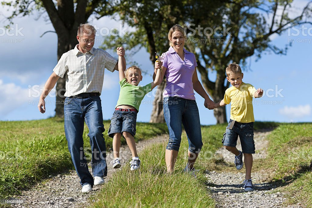 Family outdoors is running on a dirt path royalty-free stock photo