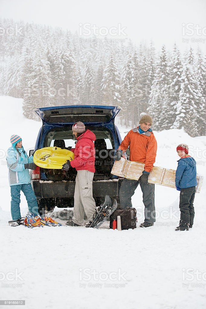 Family packing car at ski hill stock photo