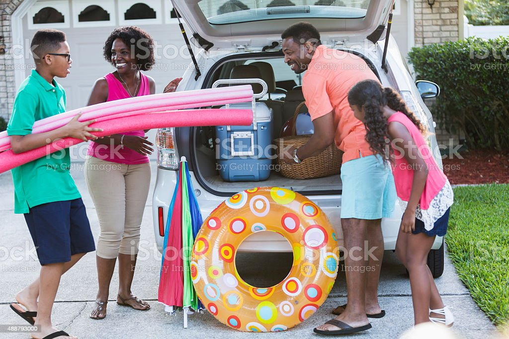 Family packing car for trip to the beach or pool stock photo