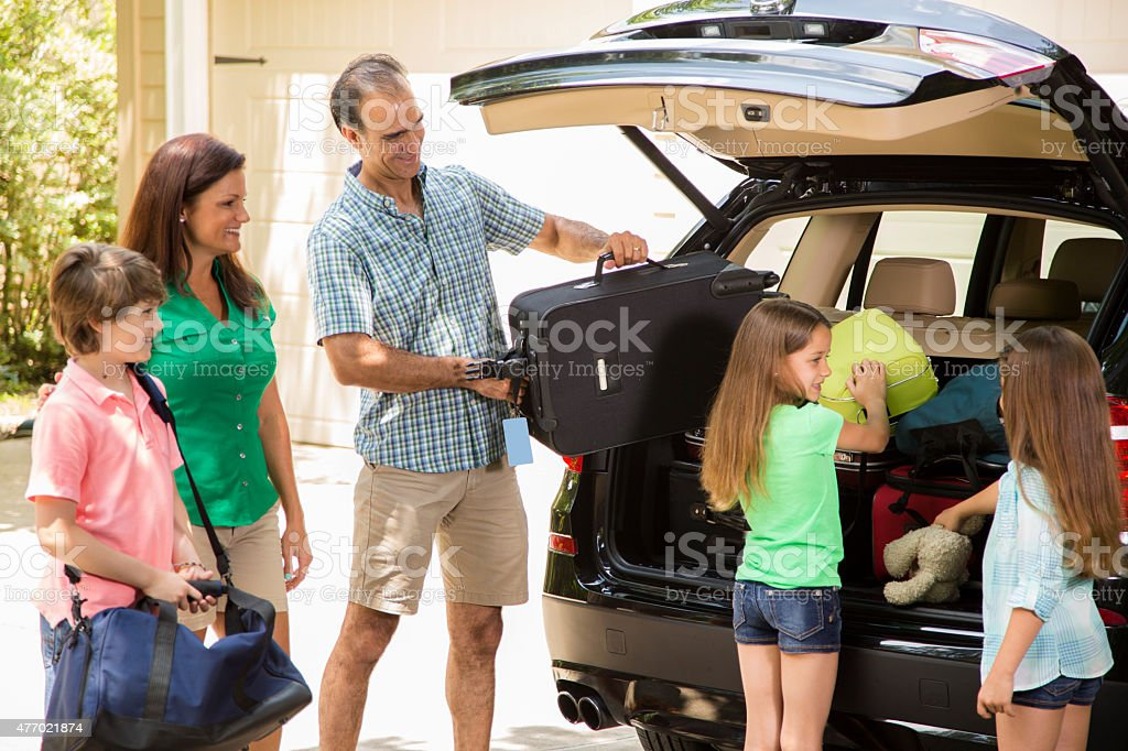 Family packing car to go on summer vacation. Parents, children. stock photo