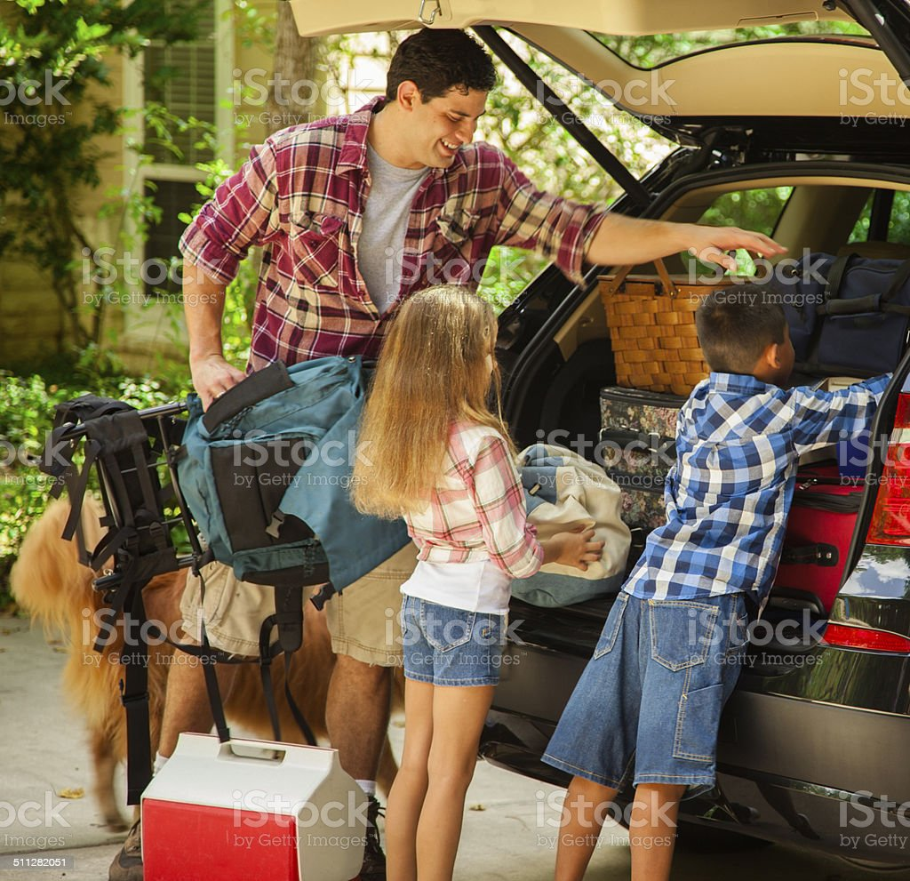 Family packing car to go on vacation. Father, children. stock photo