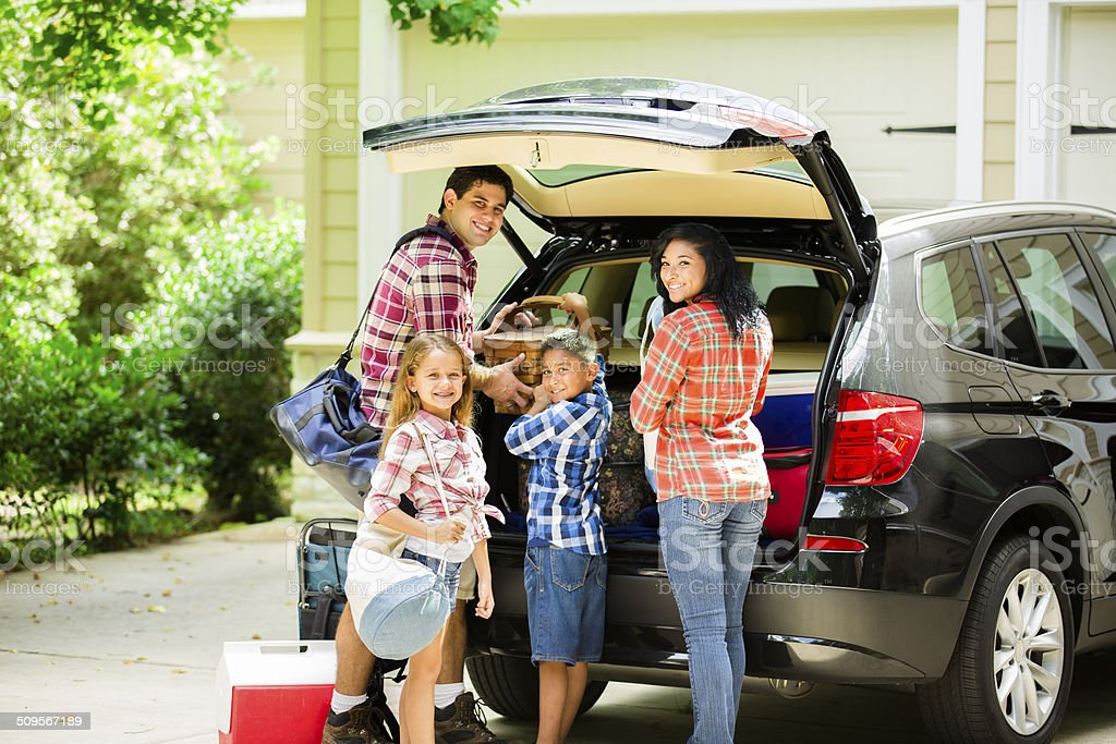 Family packing car to go on vacation. Parents, children. stock photo