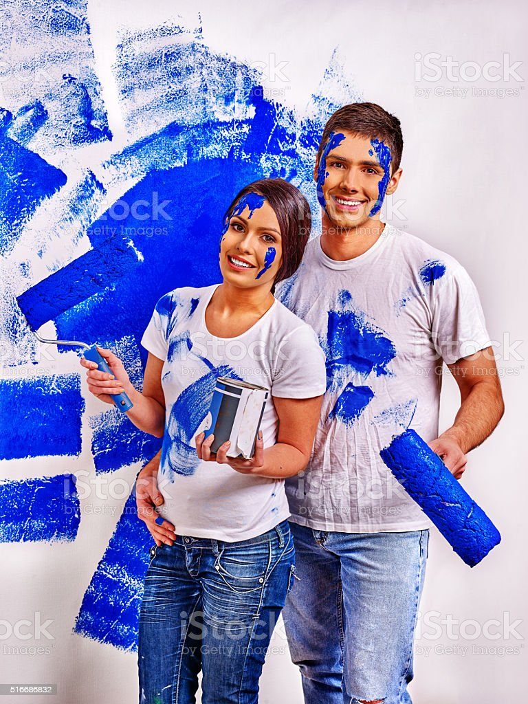 Happy newlyweds family paint in blue wall at home.