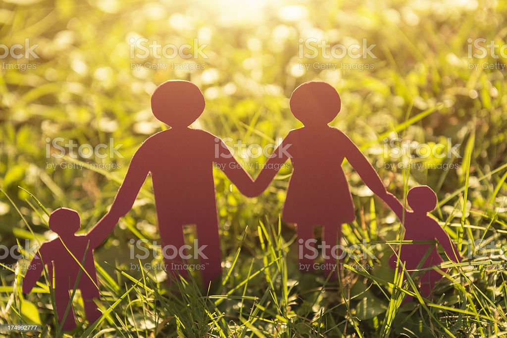 Family paper dolls on the grass at dusk royalty-free stock photo