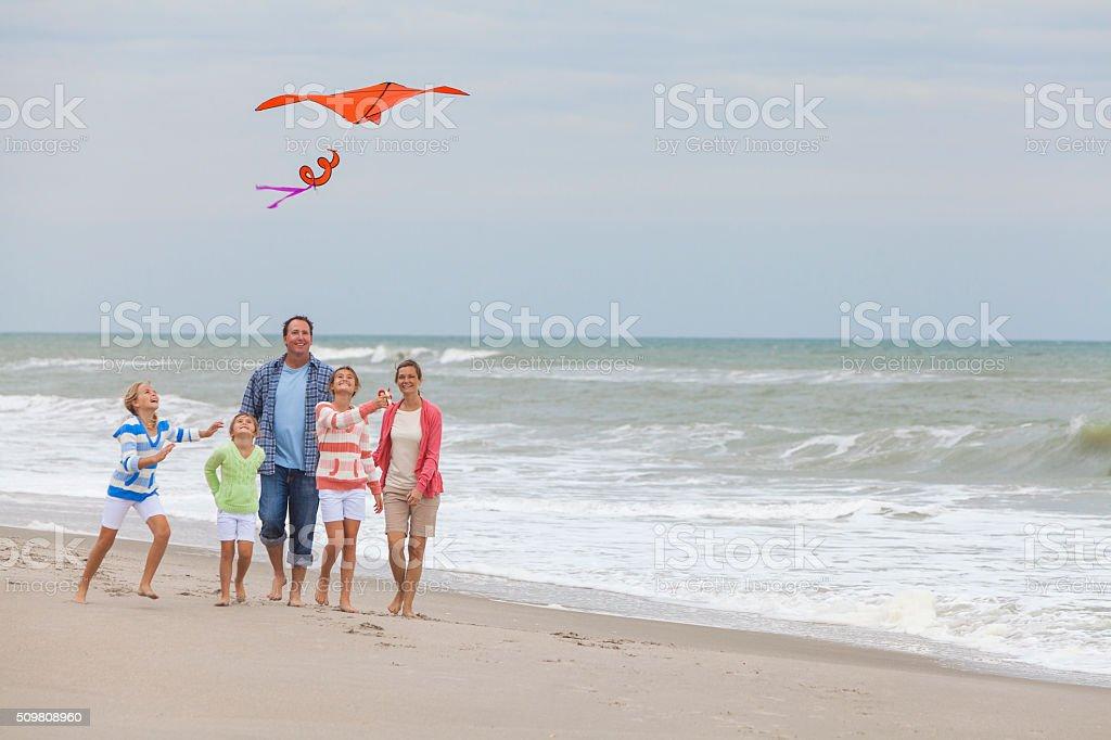 Family Parents Girl Children Flying Kite on Beach stock photo