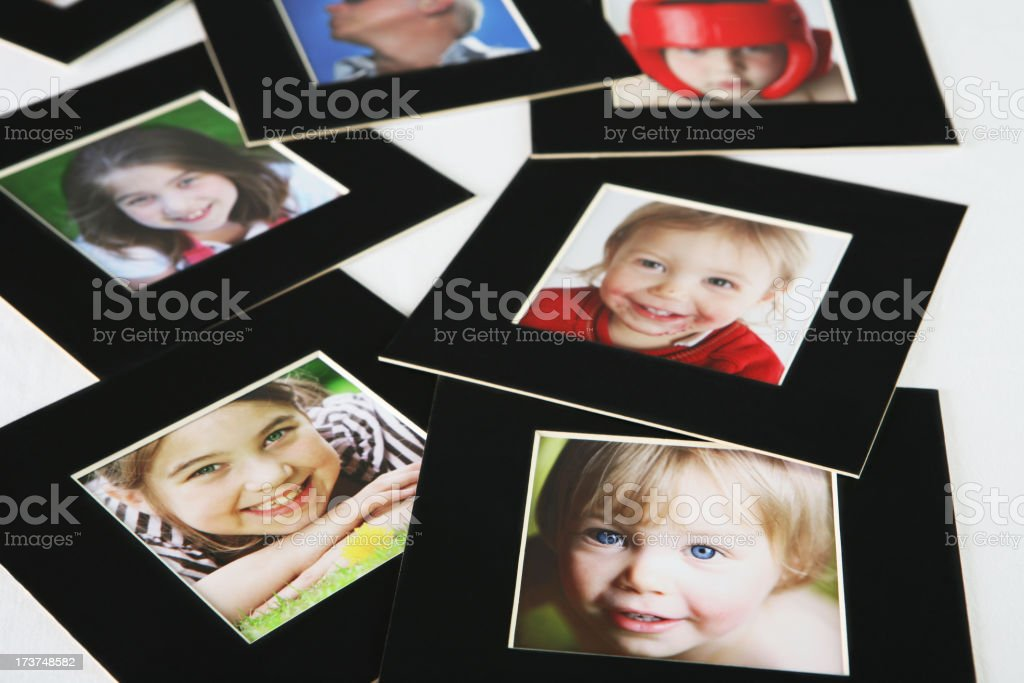 Family pictures in black frame scattered on white surface royalty-free stock photo