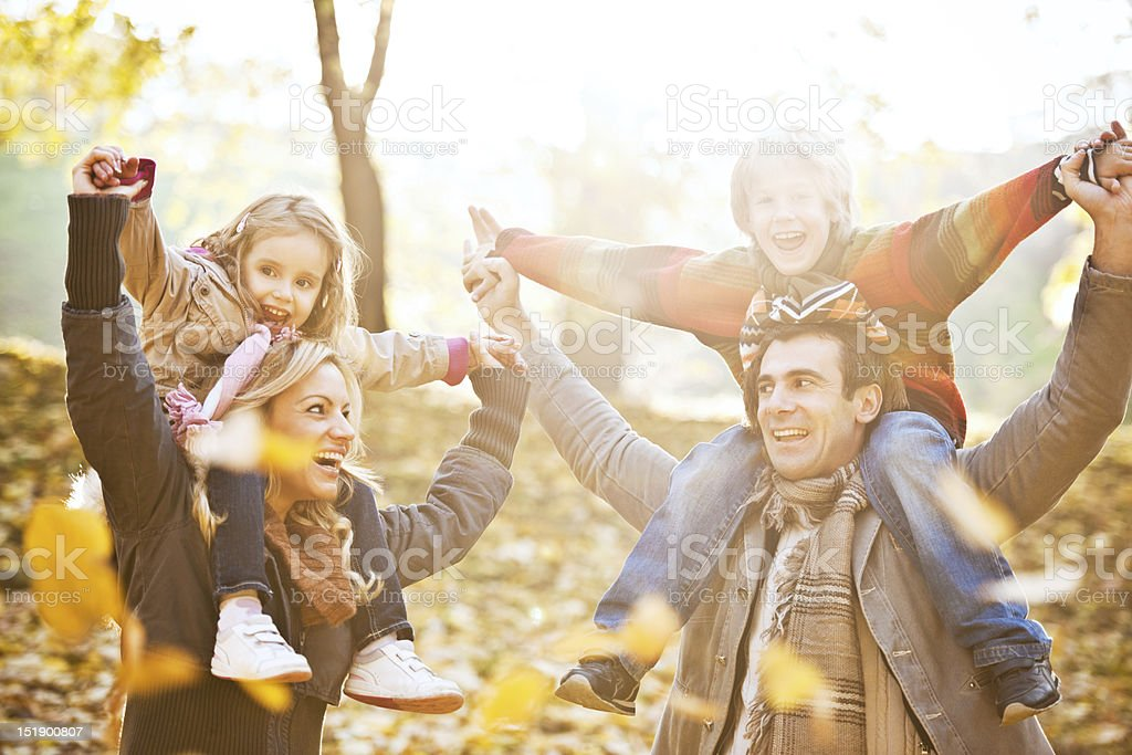 Family piggybacking their children in park. royalty-free stock photo