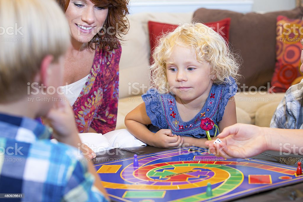Family playing an exciting board game at home stock photo