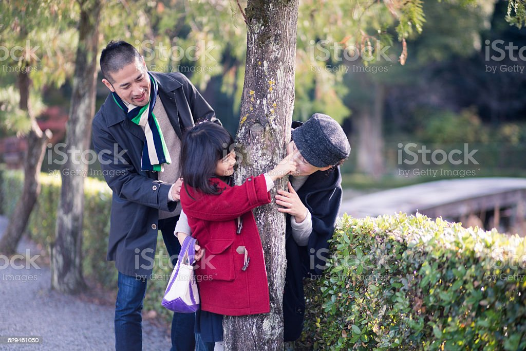 Family playing around tree in the morning stock photo