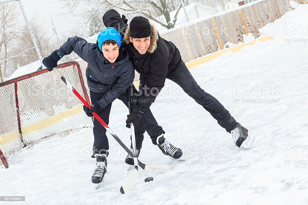 family playing at the skating rink in winter. stock photo