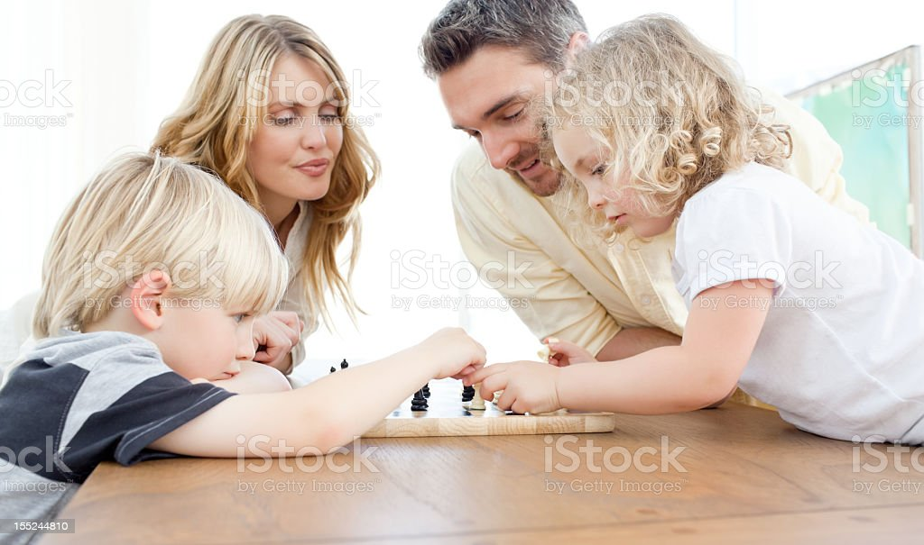 Family playing chess on a table stock photo
