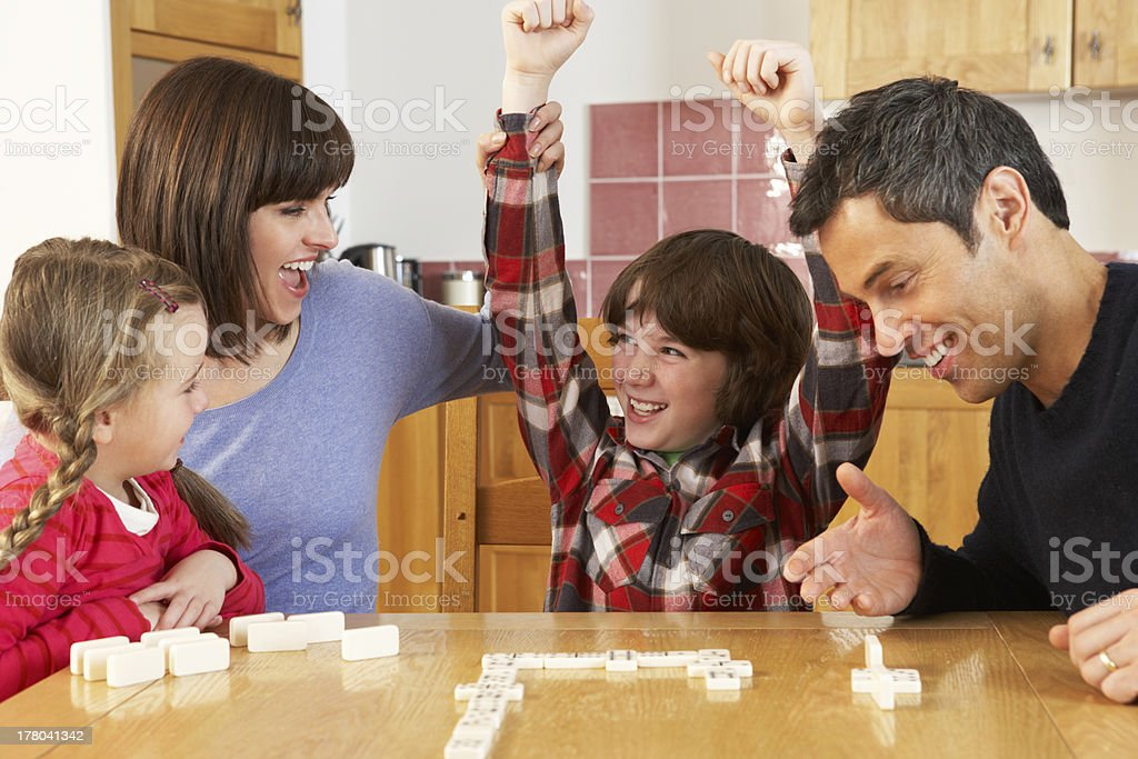Family Playing Dominoes In Kitchen stock photo