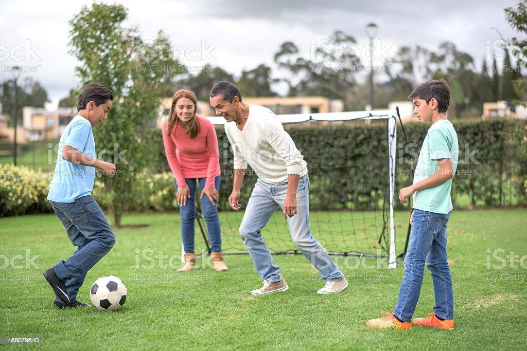 Family playing football at the park stock photo