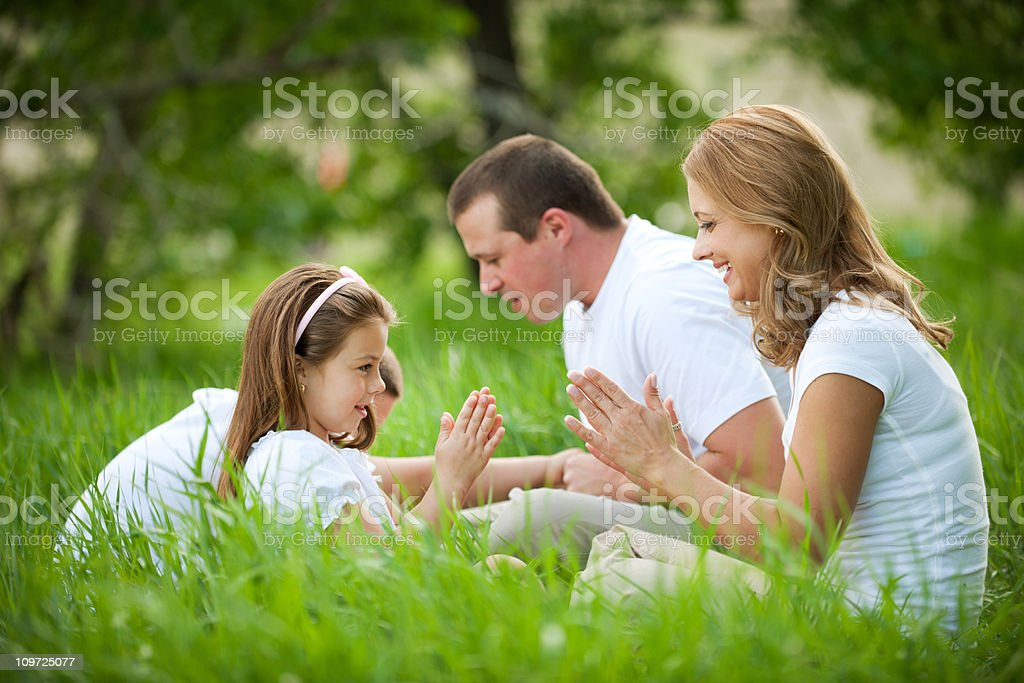 Family playing games in grass royalty-free stock photo