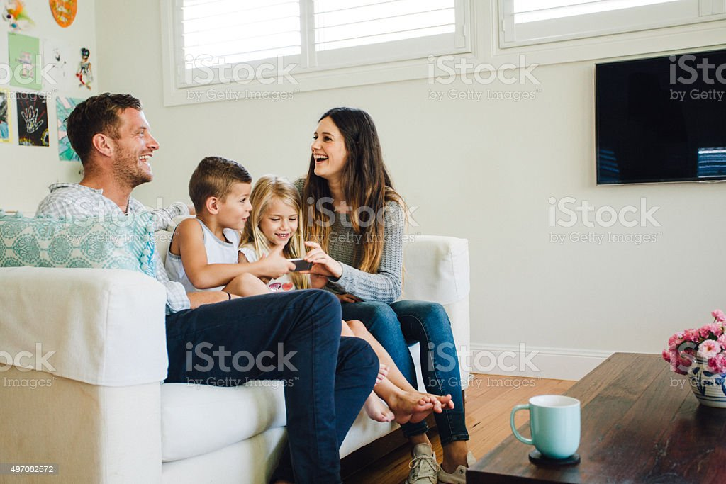 family playing games on the couch stock photo