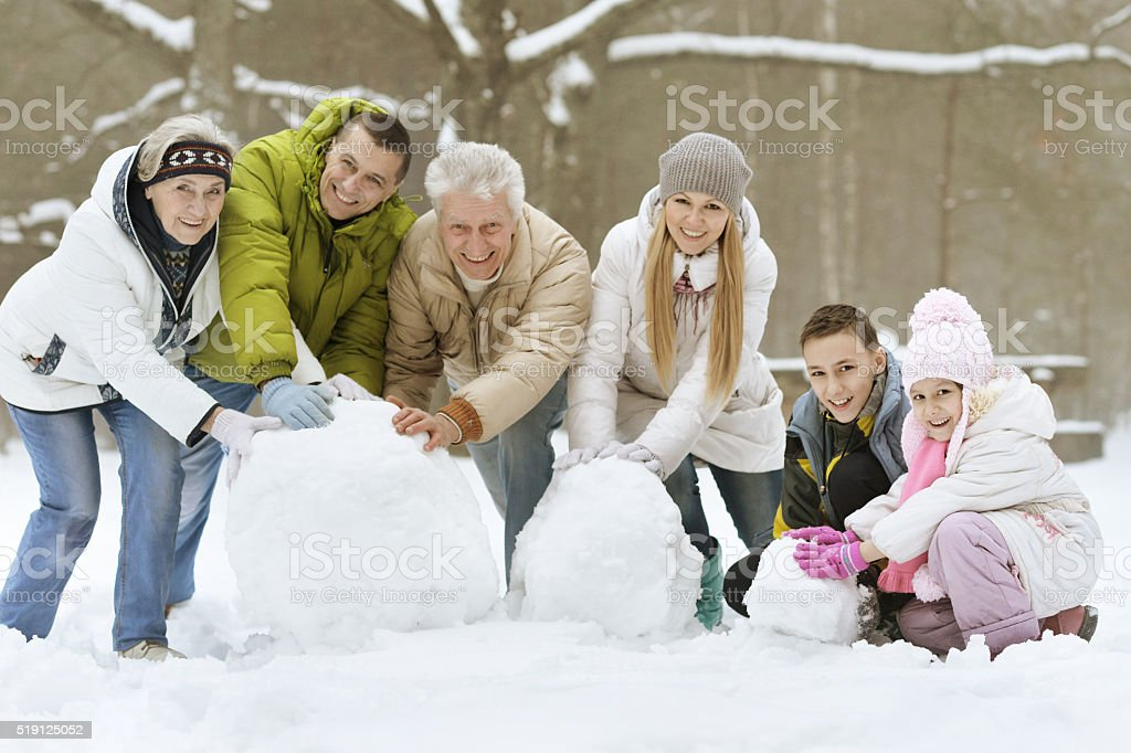 family playing in fresh snow stock photo