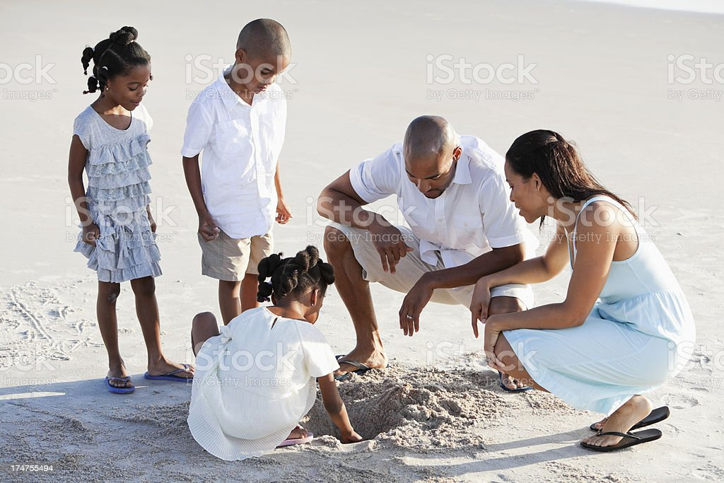 Family playing in sand at beach stock photo