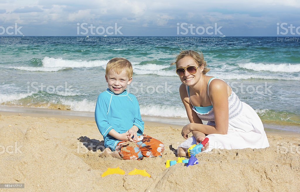 Family playing in the sand at beach royalty-free stock photo