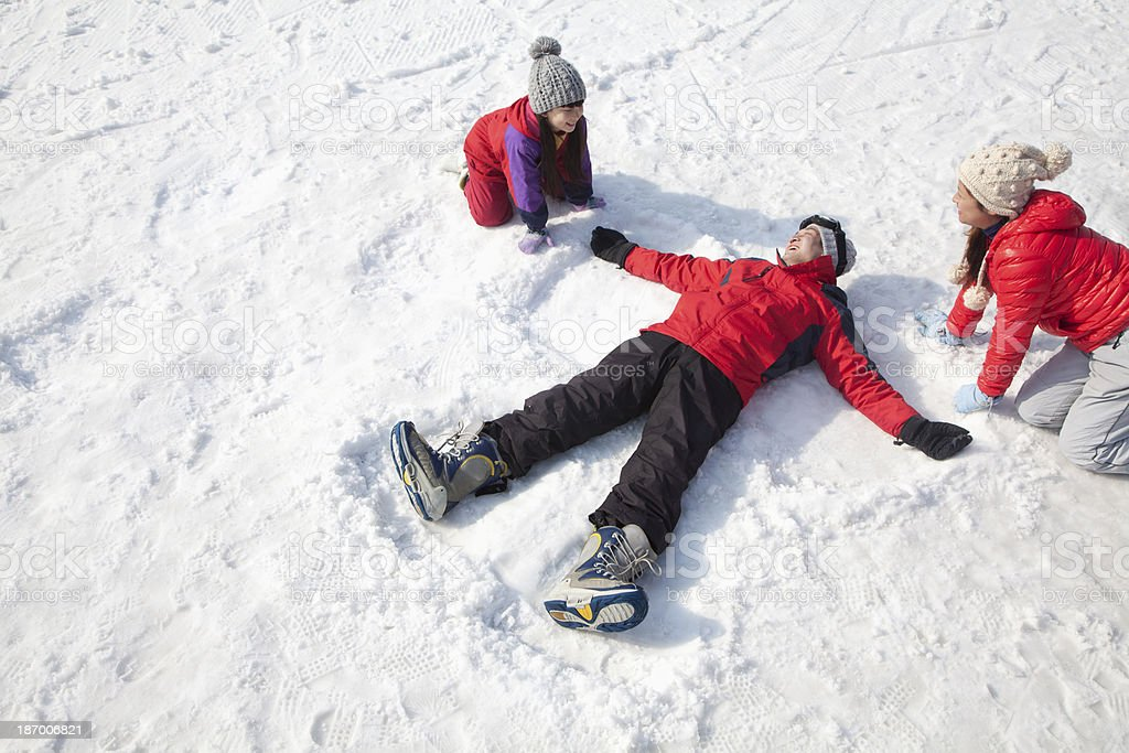 Family Playing in the Snow, Father Making Snow-Angel stock photo